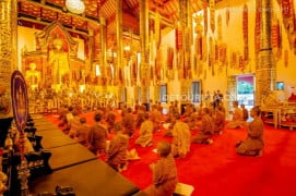 Buddhist monk apprentices and apprentices during a prayer ritual inside Wat Chedi Luang.