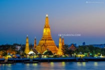 Wat Arun (temple) lit up at dusk along Chao Phraya River in Bangkok, Thailand