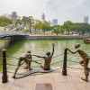 Statues of children playing by the river with a view of heritage buildings and bridges along the Singapore River at the Civic District in Singapore