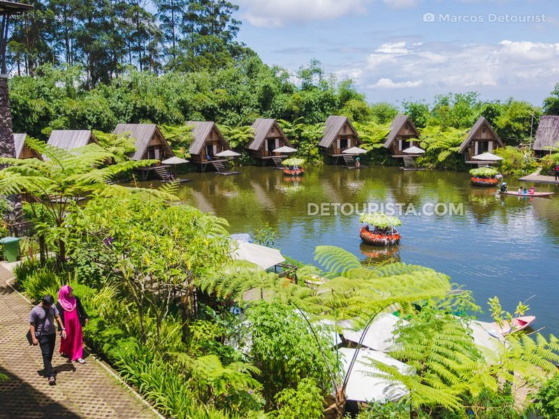 Paddle boats & traditional wooden cottages on the lake at Dusun Bambu, in Bandung, Indonesia